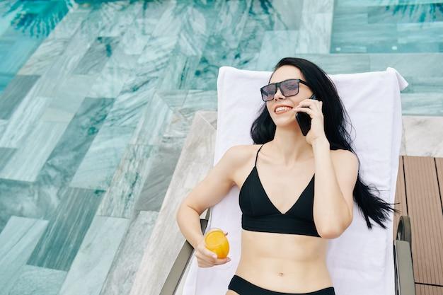 Schöne glückliche junge fit frau, die auf chaiselongue durch schwimmbad ruht, saft trinkt und am telefon spricht