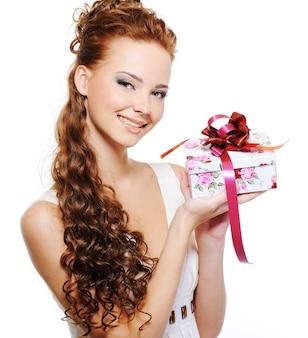 Schöne glückliche junge frau, die das geschenk über weißem hintergrund hält