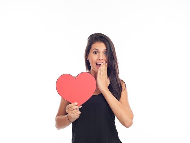 Schöne glückliche junge frau, die ein großes rotes herz für valentinstag hält