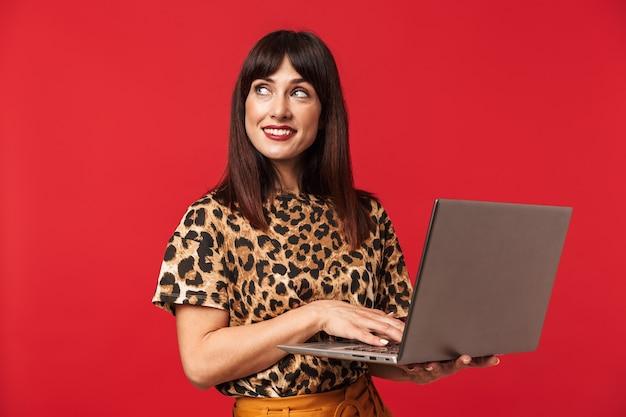 Schöne glückliche junge frau, gekleidet in tier bedrucktes hemd posiert isoliert über rote wand mit laptop-computer.