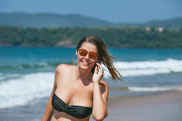 Schöne glückliche junge frau im bikini am sandigen ozeanstrand