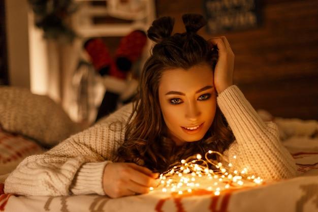 Schöne glückliche junge frau im gestrickten pullover mit festlichen lichtern auf dem bett am heiligabend