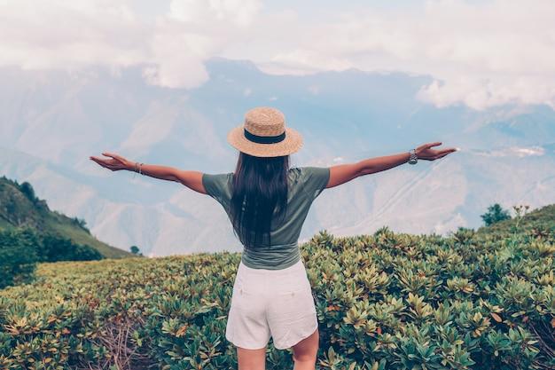 Schöne glückliche junge frau in den bergen im hintergrund des nebels