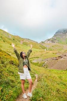 Schöne glückliche junge frau in den bergen im nebel