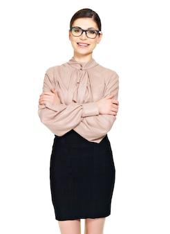 Schöne glückliche junge frau in den gläsern und im beigen hemd mit dem schwarzen rock lokalisiert auf weißem hintergrund