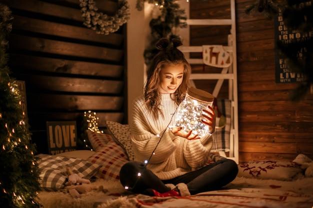 Schöne glückliche junge frau in einem gestrickten weinlesepullover mit einem magischen glas mit festlichen lichtern auf dem bett