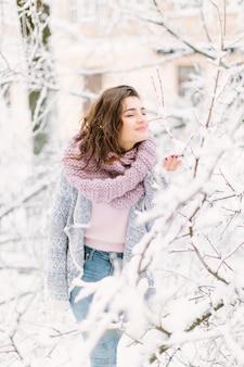 Schöne glückliche junge frau in einer blauen strickjacke der weinlesemode und in einem warmen schal gehend in die winterstadt, stehend nahe dem baum mit schnee. winterurlaub und