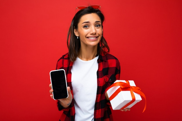 Schöne glückliche junge frau lokalisiert über rote hintergrundwand, die weißes lässiges t-shirt trägt