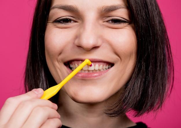 Schöne glückliche junge frau mit einzelner büscheliger zahnbürste auf leerem rosa hintergrund