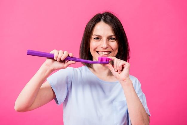 Schöne glückliche junge frau mit großer zahnbürste auf leerem rosa hintergrund