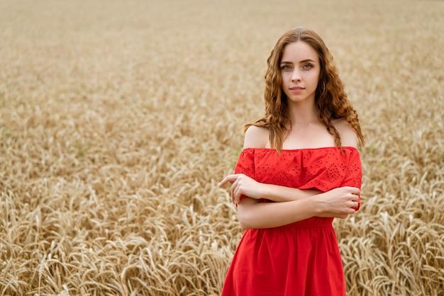 Schöne glückliche junge frau mit lockigem haar in einem roten kleid, das in einem weizenfeld aufwirft