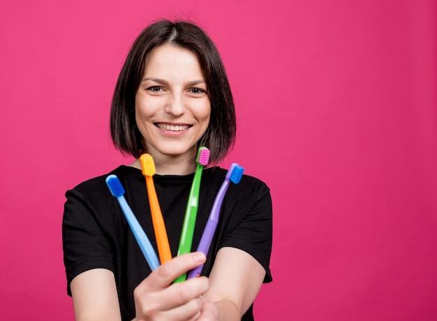Schöne glückliche junge frau mit verschiedenen farbigen zahnbürsten auf leerem rosa hintergrund