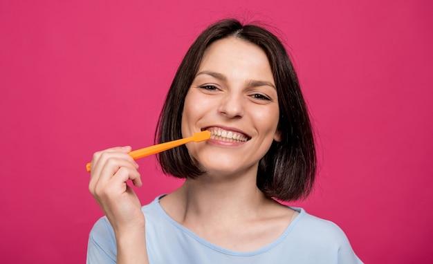 Schöne glückliche junge frau mit zahnbürste auf leerem rosa hintergrund