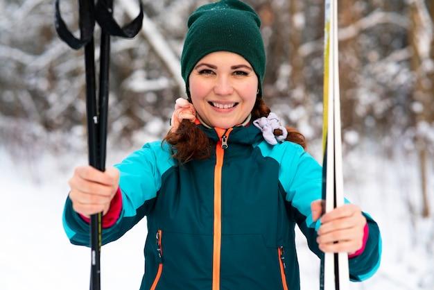 Schöne glückliche junge frau skifahrer hält ski und stöcke in händen in schneekalten wintertag im wald oder park und lächelnd