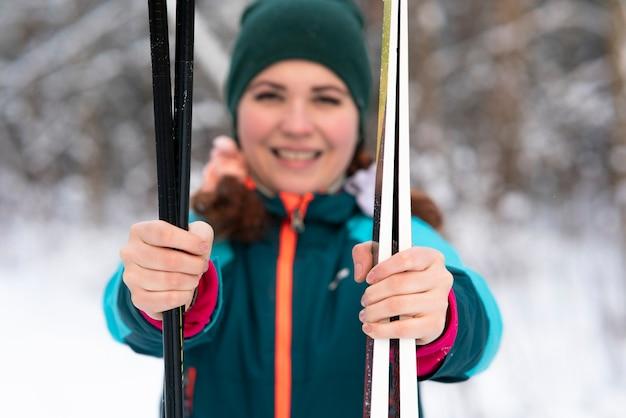 Schöne glückliche junge frau skifahrer hält ski und stöcke in händen in schneekalten wintertag in der