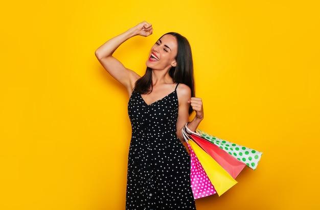 Schöne glückliche junge stilvolle brünette frau in einem kleid posiert mit vielen bunten einkaufstüten und hat spaß