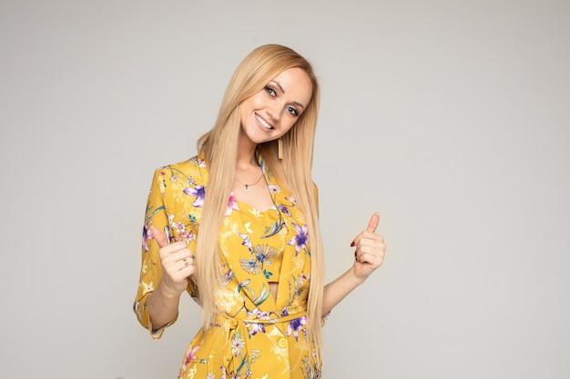 Schöne glückliche kaukasische frau mit langen blonden haaren im gelben kleid mag etwas und zeigt es