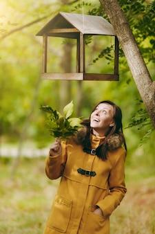 Schöne glückliche kaukasische junge lächelnde braunhaarige frau im gelben mantel, in den jeans, in den stiefeln im grünen wald. mode-modell mit herbstlaub, das unter vogelhäuschen im frühherbstpark im freien steht.