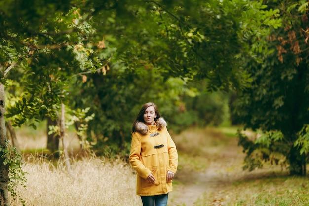 Schöne glückliche kaukasische junge lächelnde braunhaarige frau im gelben mantel, in den jeans, in den stiefeln im grünen wald. mode weibliches modell mit goldenen herbstblättern, die draußen im frühherbstpark stehen und gehen.