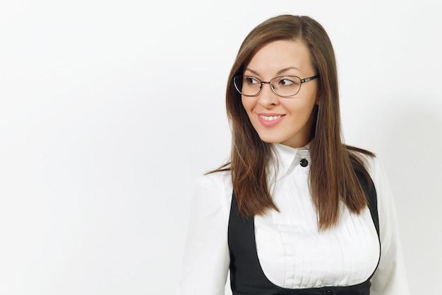 Schöne glückliche kaukasische junge lächelnde braunhaarige geschäftsfrau im schwarzen anzug, im weißen hemd und in der brille, die beiseite lokalisiert auf weißem hintergrund schaut. manager oder arbeiter. kopieren sie platz für werbung.