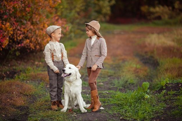Schöne glückliche kinder bruder und schwester gehen ihren hund retriever