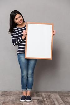 Schöne glückliche lächelnde asiatische frau im gestreiften pullover, der front betrachtet, der weißen rahmen hält