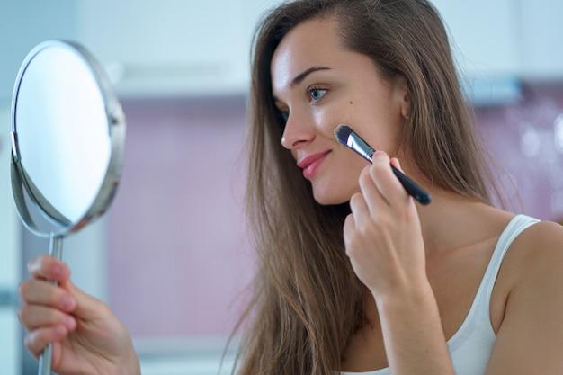 Schöne glückliche lächelnde brünette frau, die nach hause make-up unter verwendung eines kleinen runden spiegels tut und fundament auf gesicht mit make-up-pinsel am morgen aufträgt