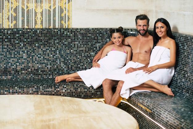 Schöne glückliche lächelnde familie in badetüchern schauen vor der kamera, während sie in der sauna oder im hamam entspannen. urlaubs- und spa-verfahren