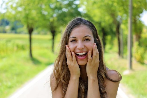 Schöne glückliche lächelnde frau, die ihr gesicht mit den händen im freien hält
