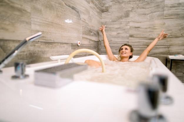 Schöne glückliche lächelnde frau, die im whirlpool im wellnesscenter genießt und sich entspannt, professionelle hydromassage hat und arme hochhält