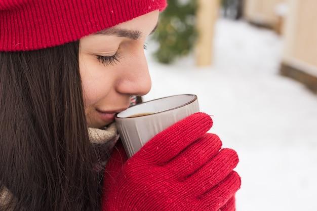Schöne glückliche lächelnde frau mit einer tasse im winter auf der straße