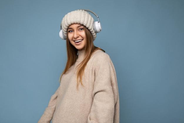 Schöne glückliche lächelnde junge blonde frau, die beige winterpullover und hut isoliert trägt