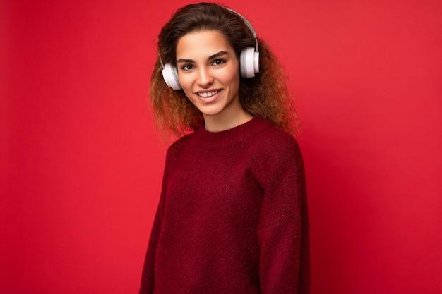 Schöne glückliche lächelnde junge brünette lockige frau, die dunklen roten pullover lokalisiert trägt