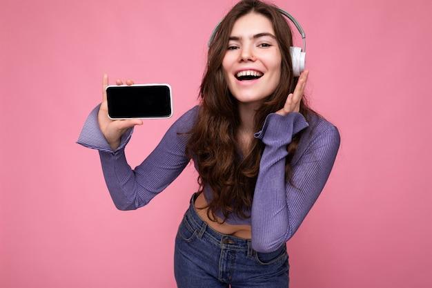 Schöne glückliche lächelnde junge frau, die stilvolles lässiges outfit auf der hintergrundwand isoliert trägt
