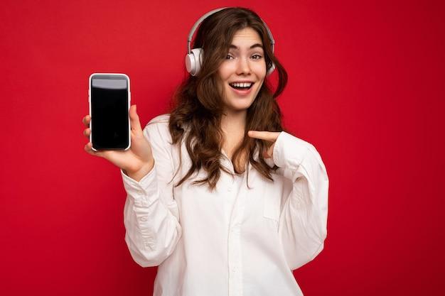 Schöne glückliche lächelnde junge frau, die stilvolles lässiges outfit trägt, das auf der hintergrundwand lokalisiert wird?