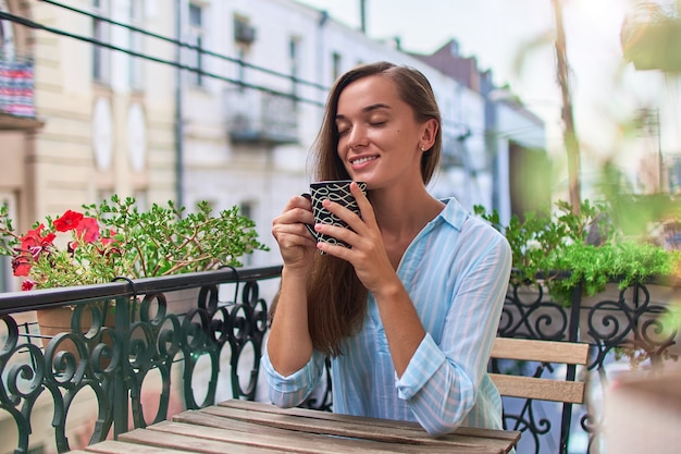 Schöne glückliche lächelnde romantische frau mit geschlossenen augen, die aromatischen kaffee auf dem balkon am frühen morgen in der stadt genießen