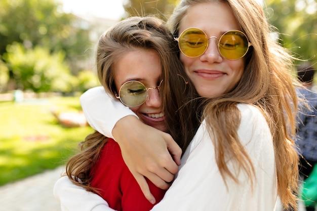 Schöne glückliche mädchen, die draußen an sonnigem tag gehen. schöne schöne frau in hellen gläsern umarmt ihre freundin und schloss die augen mit großem lächeln, besten freunden, schwestern, positiver stimmung