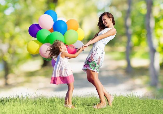 Schöne glückliche mutter mit tochter, die spaß auf der grünen wiese mit bunten luftballons hat