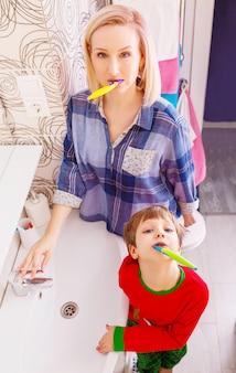 Schöne glückliche mutter und kleiner sohn in putzenden zähnen des badezimmers zusammen