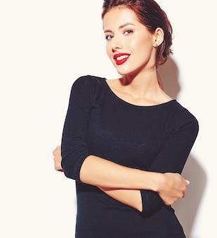 Schöne glückliche nette reizvolle brunettefrau im beiläufigen schwarzen kleid mit den roten lippen auf weißem hintergrund