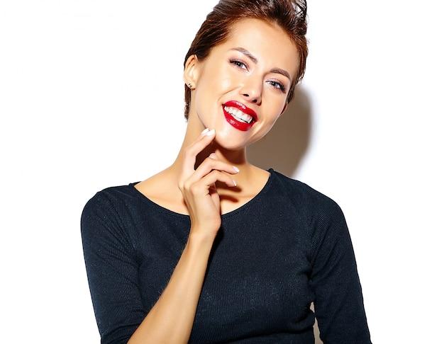 Schöne glückliche nette reizvolle brunettefrau im beiläufigen schwarzen kleid mit den roten lippen auf weißer wand