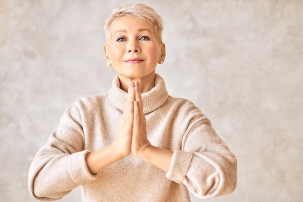 Schöne glückliche pensionierte frau, die gemütlichen pullover und kurze frisur betend betet