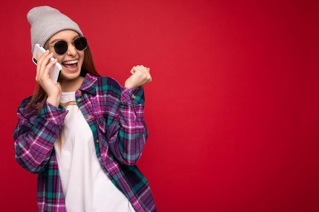 Schöne glückliche positive junge blonde frau, die purpurrotes hemd des hipsters und beiläufiges weißes t-shirt trägt