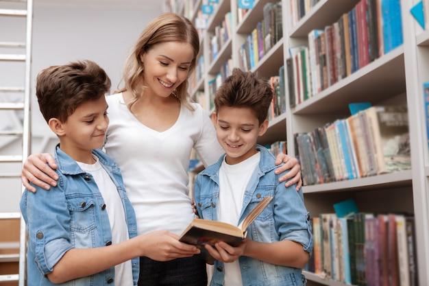 Schöne glückliche reife frau, die ein buch an der bibliothek mit ihren zwei zwillingssöhnen liest.
