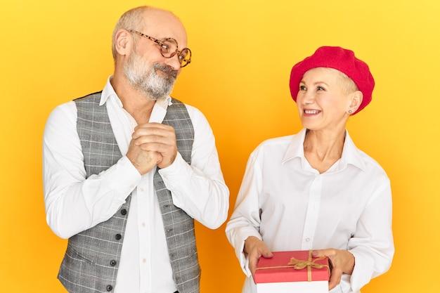 Schöne glückliche reife frau in der roten baskenmütze, die geburtstagsgeschenk vom ehemann empfängt, der ihr von ganzem herzen gratuliert. trauriger schuldiger mann, der wiedergutmachung für seine schuld leistet und frau mit geschenk gewinnt
