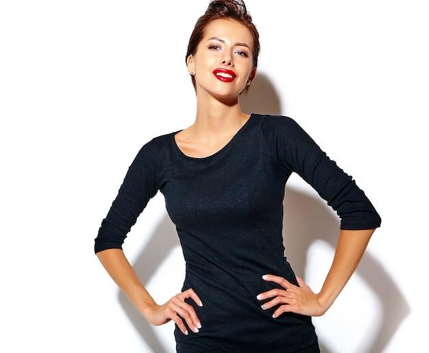 Schöne glückliche sexy brunettefrau im zufälligen schwarzen kleid mit den roten lippen auf weißer wand