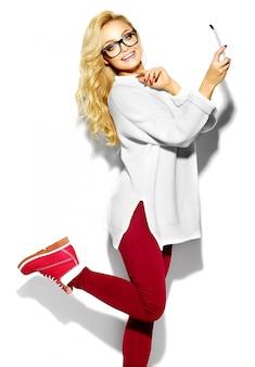 Schöne glückliche süße süße lächelnde blonde frau in lässigen weißen pulloverkleidung des lässigen hipsters, in den gläsern, die selfie nehmen