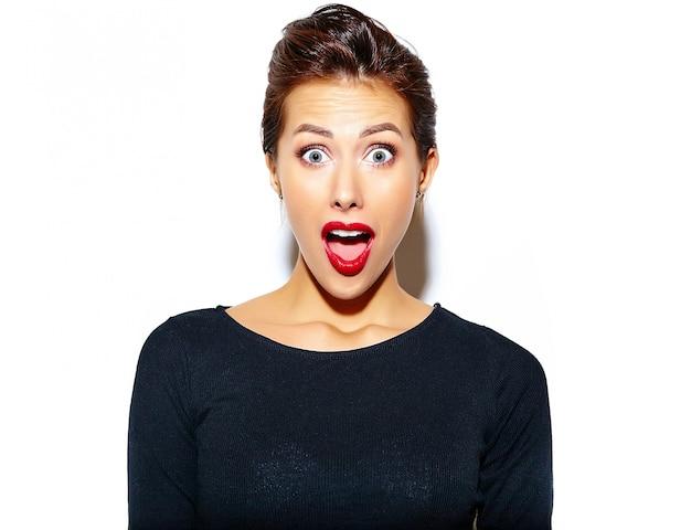 Schöne glückliche überraschte sexy brunettefrau im zufälligen schwarzen kleid mit den roten lippen auf weißer wand