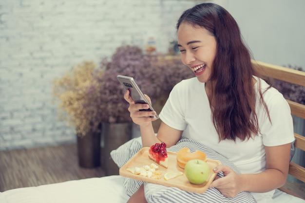 Schöne glückliche yong-frau, die frühstück mit der frucht und kuchen sprechen mit intelligentem telefon auf bett, prozessfilterweinlese isst