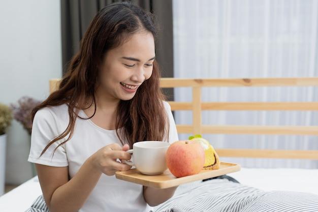 Schöne glückliche yong-frau, die frühstück mit frucht und kuchen auf bett isst